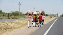 Migrant workers and their family members walk along a highway in a desperate bid to return to their village.
