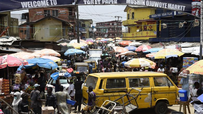 Mọi người đi bộ trong một khu chợ đông đúc bất chấp trật tự khoảng cách xã hội, để mua sắm vào phút cuối trước giờ giới nghiêm, tại Chợ Mushin ở Lagos.