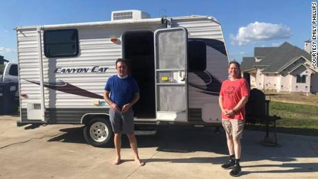 Dr. Jason Phillips (left) and Dr. Craig Reese Brockman with a donated camper that Brockman will use to prevent the risk of passing along the coronavirus to his family.