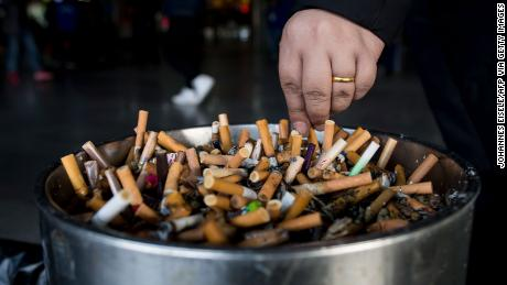 In this photo taken on February 28, 2017, a man grinds out his cigarette in an ashtray at a railway station in Shanghai.   Shanghai widened its ban on public smoking March 1 as China's biggest city steps up efforts to stub out the massive health threat despite conflicts of interest with the state-owned tobacco industry.  / AFP / Johannes EISELE        (Photo credit should read JOHANNES EISELE/AFP via Getty Images)