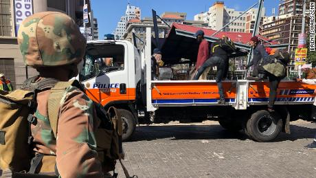 Homeless South Africans in Johannesburg are loaded on the back of a police truck where they were told they would be taken to a shelter to stay during the  lockdown.