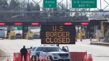 US Customs officers stand beside a sign at the US-Canada border in Lansdowne, Ontario, on March 22, 2020.