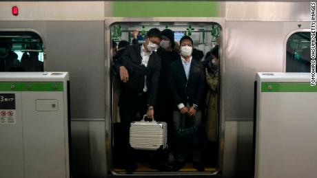 Commuters wearing face masks ride on a train on March 26, 2020 in Tokyo, Japan.