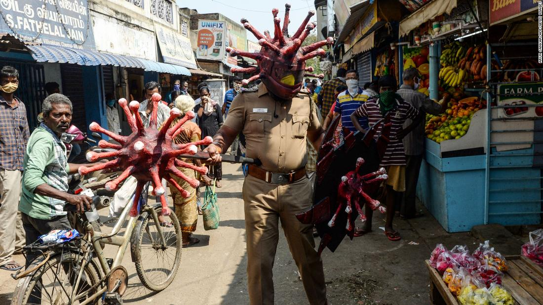 A police officer wearing a coronavirus-themed outfit walks in a market in Chennai, India, to raise awareness about social distancing.