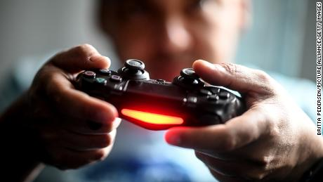 02 April 2020, Berlin: A young man plays in front of the television with the Playstation game console. To prevent infection with the corona virus, many people spend their free time at home. (Photo by Britta Pedersen/picture alliance via Getty Images)