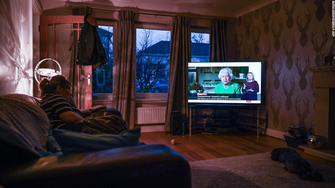 "A woman in Glasgow, Scotland, watches Britain's Queen Elizabeth II <a href=""https://www.cnn.com/2020/04/05/uk/queen-elizabeth-ii-coronavirus-address-gbr-intl/index.html"" target=""_blank"">give a television address</A> regarding the coronavirus pandemic."