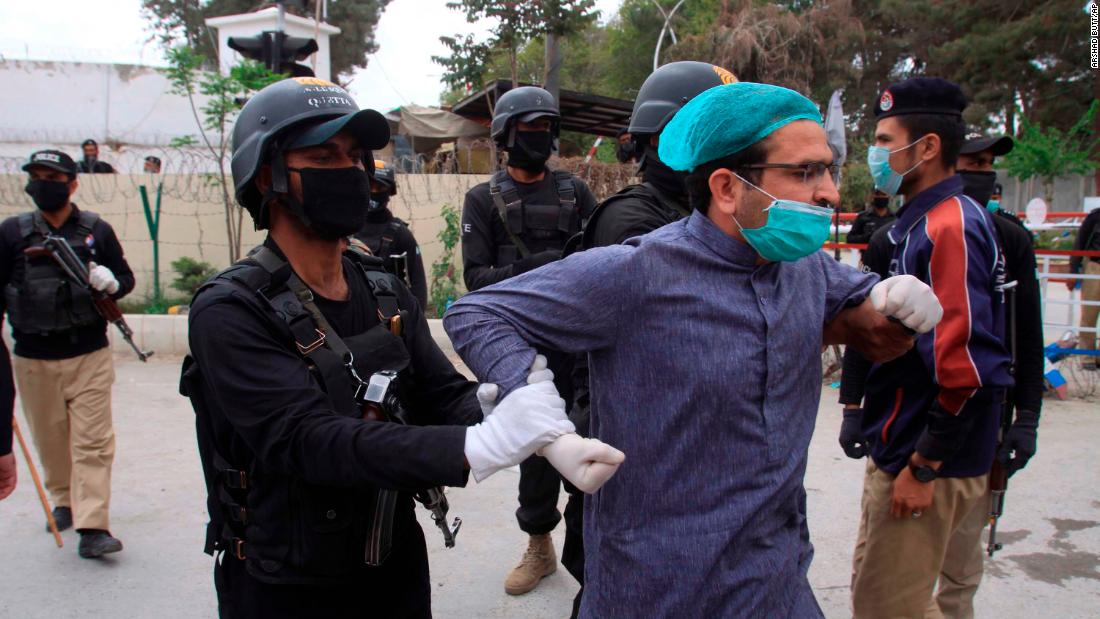 Police detain a doctor in Quetta, Pakistan, who was among dozens of health care workers protesting a lack of personal protective equipment on April 6.