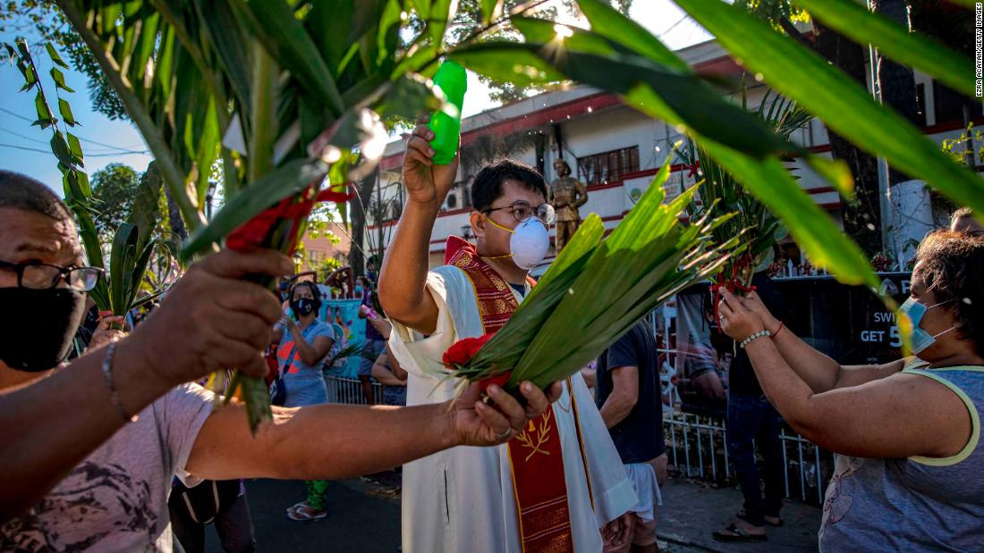 A Catholic priest sprinkles holy water on devotees during Palm Sunday celebrations in Quezon City, Filippine, di domenica, aprile 5.