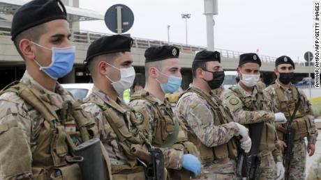 Soldații libanei, purtând echipament de protecție, stau de pază pe Aeroportul Internațional Beirut pe 5 aprilie, înainte de întoarcerea resortisanților care se întorc.