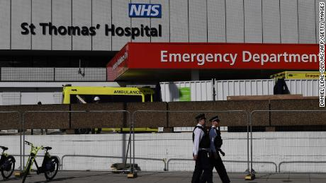 British police officers stand on duty outside St Thomas' Hospital in central London, where Britain's Prime Minister Boris Johnson is in intensive care on Tuesday, April 7.