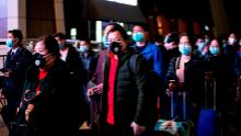 Passengers wear facemasks as they form a queue at the Wuhan Wuchang Railway Station in Wuhan, early on April 8, as they prepare to leave the city for the first time in more than ten weeks.