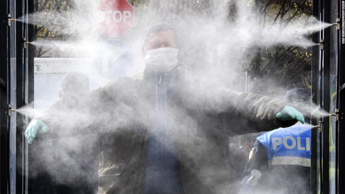 A man is sprayed with disinfectant prior to going to a market in Tirana, Albania, di lunedi, aprile 6.