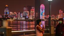 People stand near the Yangtze River in the city of Wuhan, on April 6. In recent weeks, officials have gradually eased some of the lockdown measures, allowing a limited number of residents to leave their residential compounds for a short time.