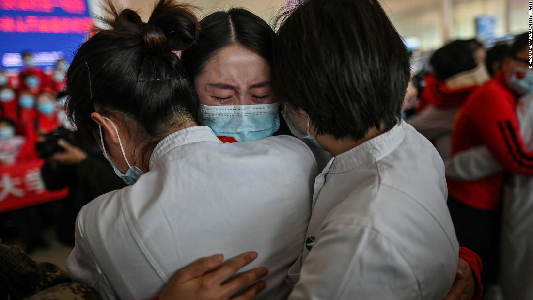 "A medical staff member from China's Jilin province, centro, cries while hugging nurses from Wuhan on April 8. Wuhan was <a href =""https://www.cnn.com/2020/04/07/asia/coronavirus-wuhan-lockdown-lifted-intl-hnk/index.html"" target =""_blank&ampquott;>reopening its borders</un> dopo 76 giorni."
