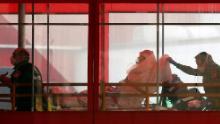 Emergency medical technicians wheel a patient into Elmhurst Hospital Center's emergency room,.