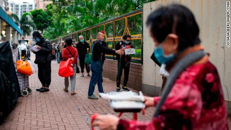 Chu Kin Lik, 61, makes sure people keep their distance as they wait for dinner at Impact HK's meal service on Tuesday, April 7
