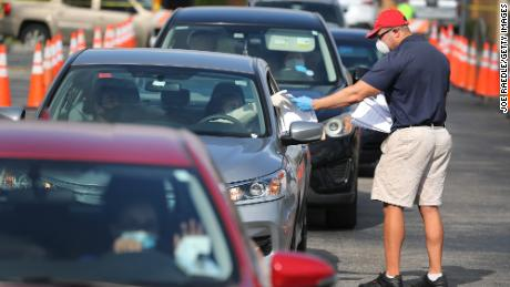 Miguel Diaz, who works for the the Florida city of Hialeah, hands out unemployment applications to people in their vehicles in front of a library Wednesday.