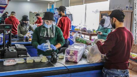 Pe 23 martie, angajații lucrează cu scuturi de față și mănuși de protecție într-un magazin din Batroun, în nordul Libanului.
