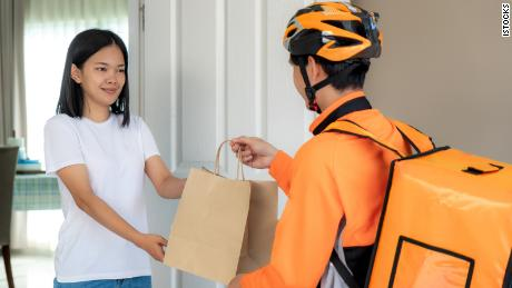 woman receives food delivery service at door paid with credit card