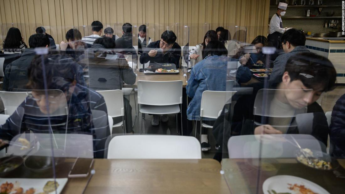 Employees of Hyundai Card, a credit card company, sit behind protective screens as they eat in an office cafeteria in Seoul, South Korea, 四月に 9.