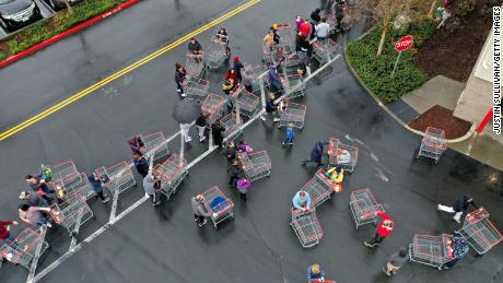 Hundreds of people line up to enter a Costco store in California.
