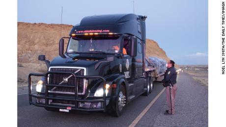 Un ofițer de poliție din Națiunea Națională oferă șoferului unui camion informații despre portbagajul națiunii.