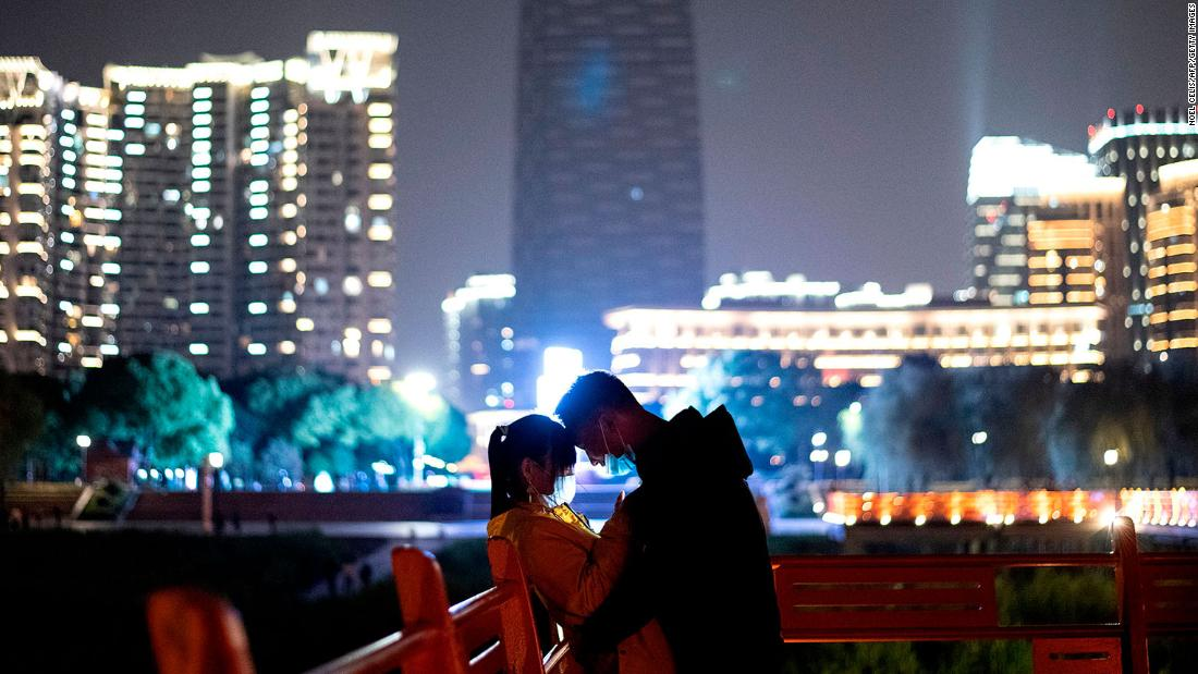 A couple stands in a park along the Yangtze River in Wuhan, Cina.