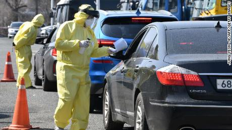 Medical staff guide drivers with suspected coronavirus symptoms at a drive-thru testing facility in Goyang, north of Seoul, on February 29.