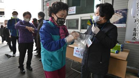 A South Korean woman wears plastic gloves and a mask as she prepares to cast her ballot during April's election.