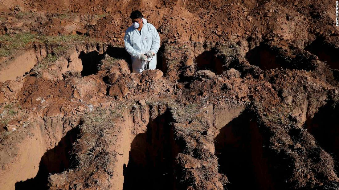 A cemetery worker pauses while digging graves at the San Vicente cemetery in Cordoba, Argentina, 四月に 14.