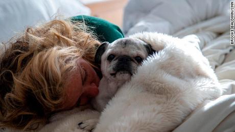 Laid very low by the coronavirus, Baldwin naps with her dog Pugsley.