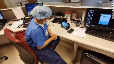 A health care provider at North Shore University Hospital uses an Echo Show to communicate with a coroanvirus patient.