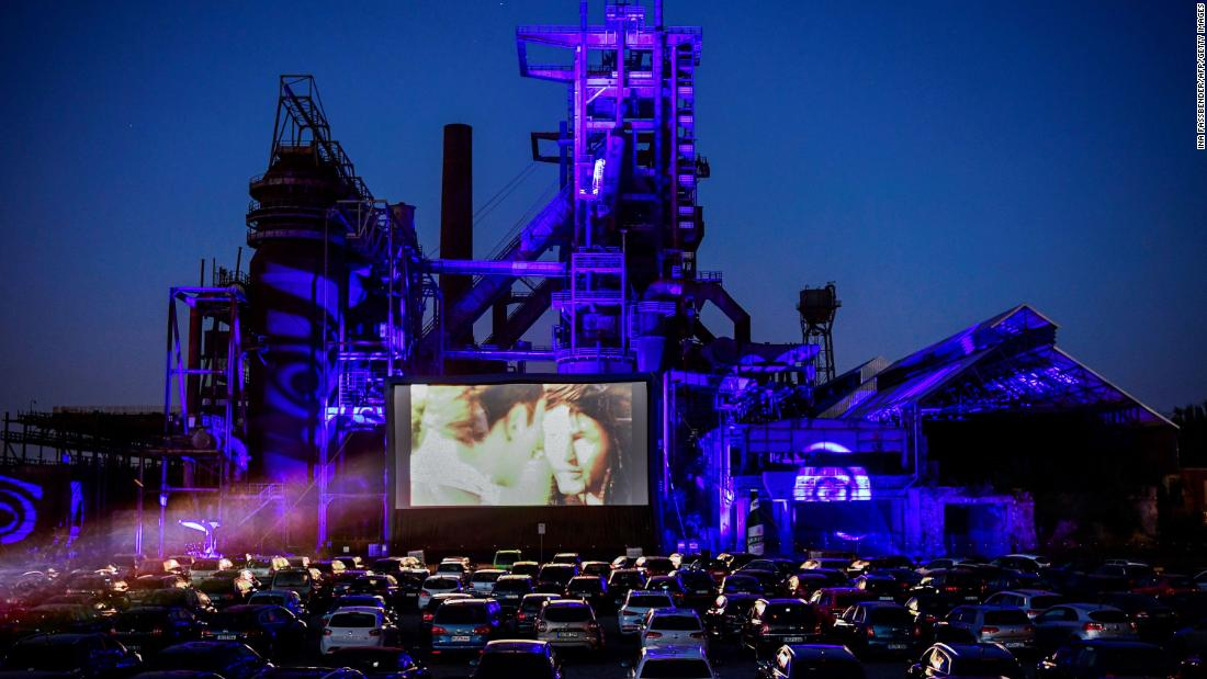 Cars sit at a newly opened drive-in cinema in Dortmund, Germania, in aprile 17. It's in front of a former blast furnace.