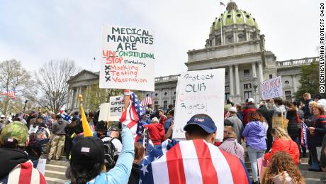 """People take part in a """"reopen"""" Pennsylvania demonstration on April 20, 2020 in Harrisburg, Pennsylvania. - Hundreds have protested in cities across America against coronavirus-related lockdowns -- with encouragement from President Donald Trump -- as resentment grows against the crippling economic cost of confinement."""