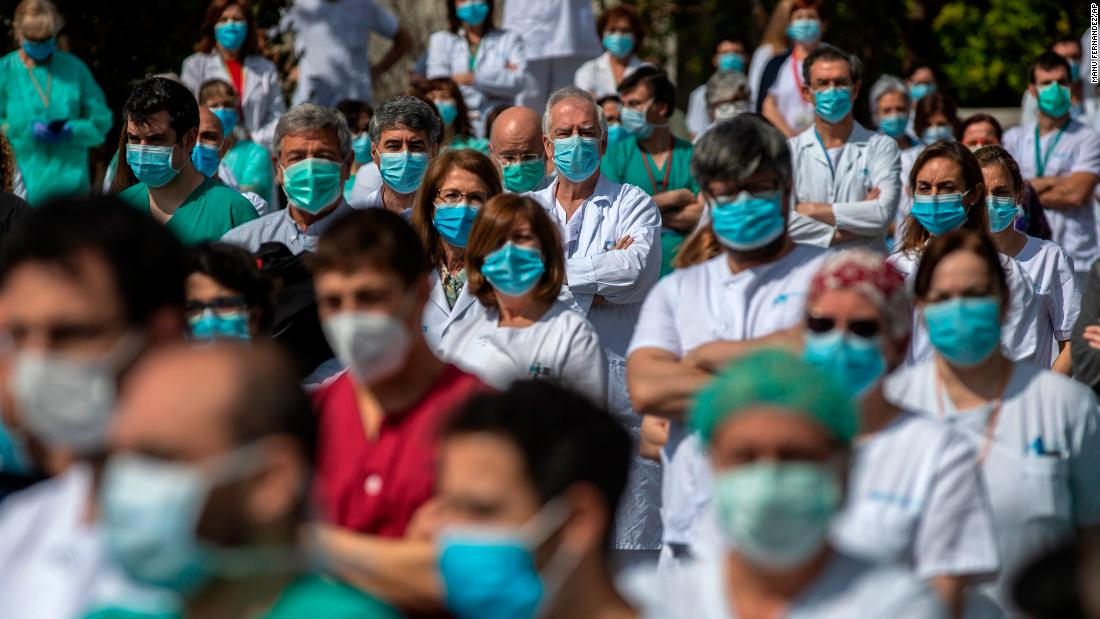 Health workers at Madrid's La Paz Hospital hold a minute of silence to remember Joaquin Diaz, the hospital's chief of surgery who died because of the coronavirus.