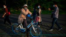 Una mujer con una máscara facial descansa en una bicicleta a lo largo del lago del este en Wuhan después de que se levantó su encierro.