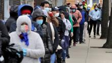 Hundreds impacted by the Covid-19 virus outbreak wait in line for boxes of food at a Salvation Army center in Chelsea, Mass.
