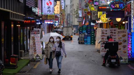 Two women wear face masks in Seoul. Countries in which covering one's face is a social norm have generally fared better during the pandemic.