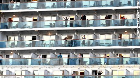 People wave as the cruise ship Ruby Princess departs from Port Kembla, some 80 kilometres south of Sydney, on April 23, after a few hundred virus-free crew members disembarked to begin the process of repatriation to their home countries.