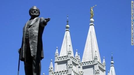 A statue of Brigham Young, second president of the Church of Jesus Christ of Latter-day Saints stands in the center of Salt Lake City, Utah with the Mormon Temple spires in the background.