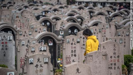 A woman decorates a grave during the Qing Ming festival, also known as Tomb Sweeping Day, at a cemetery in Shanghai on April 6, 2018. Traditional religious practice is growing in China, but the government tightly controls foreign faiths.
