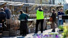 """An employee wears a vest reading """"Keep distance. Stop Covid-19"""" as customers look at plants at the Slottstradgarden Ulriksdal garden centre in the Ulriksdal Palace park in Stockholm on April 21."""