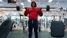 A man, one of two people at a gym, lifts weight in Lilburn, Georgia on April 24.