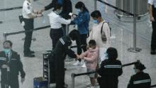 Passengers receive quarantine tracking wrist bands at Hong Kongs international airport on March 19.
