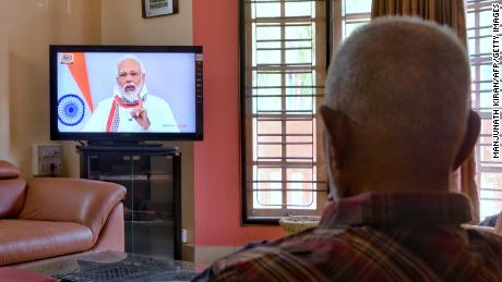 A senior citizen watches Modi address the nation on a television broadcast during India's government-imposed coronavirus lockdown.