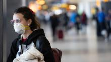 A passenger wearing a mask prepares to board a flight at the Seattle-Tacoma International Airport on March 15.