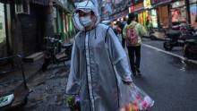 A person wearing a face mask as a preventive measure against the spread of the COVID-19 novel coronavirus carries groceries in a neighbourhood in Wuhan in China's central Hubei province on April 20.