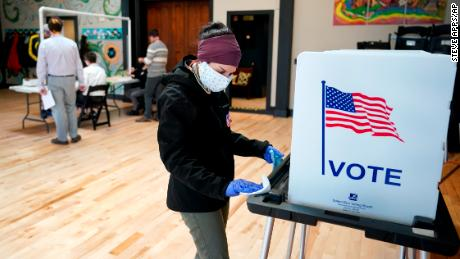 A Wisconsin election staffer cleans a votnig booth after it was used on April 7 in Madison. The state held its elections during a stay-at-home order.