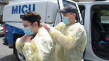 Storzillo and Incorvaia prep to enter a house with a suspected Covid-19 patient.