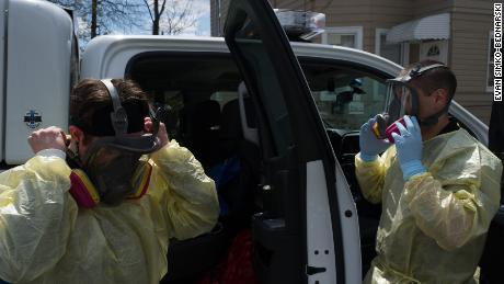 Paramedics Alex Storzillo and Jim Incorvaia adjust their respirators before entering a house.